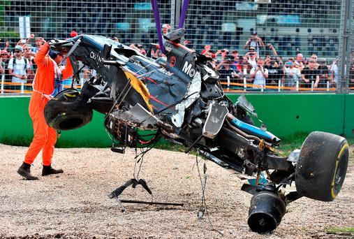 Fernando Alonso's car being removed from the track following a crash during the Australian Grand Prix in Melbourne Photo: AP Photo/Theo Karanikos