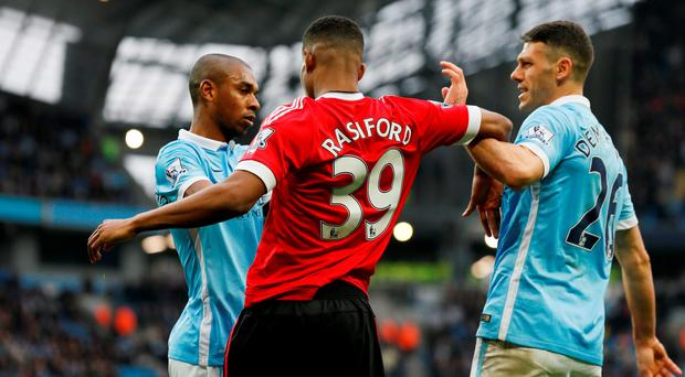 Manchester City's Martin Demichelis and Fernandinho clash with Manchester United's Marcus Rashford. Photo: Reuters