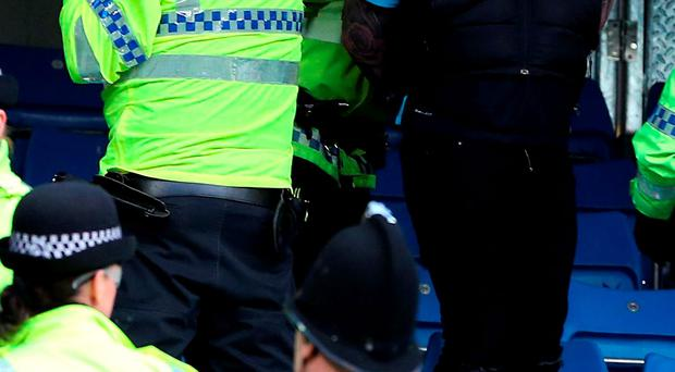 A Manchester City supporter is reprimanded by Police after the final whistle in the Barclays Premier League match at the Etihad Stadium