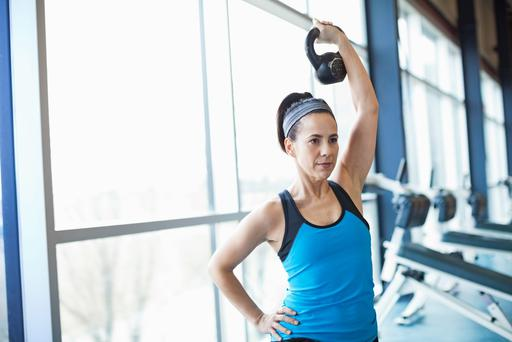 Woman exercising with kettlebell in fitness center