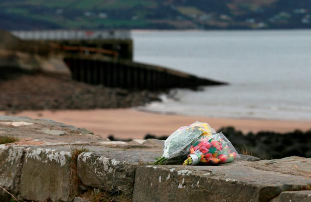 Flowers left at the scene at Buncrana Pier in Co Donegal after five people, including at least two children, have been killed and a baby girl is in hospital after a car they were in slipped from the pier