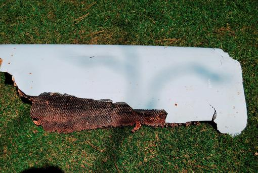 The curved piece of debris which may be part of the missing Malaysia Airlines Flight MH370, in Wartburg, 37km (22 miles) out of Pietermaritzburg, South Africa, Monday, March 7, 2016. (Candace Lotter via AP)