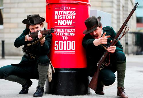 Andrea Farrell and Dave Swift, who play the parts of rebel snipers in one of the stories from the An Post 'GPO Witness History' campaign, at the red postbox at the Royal College of Surgeons on St Stephen's Green, Dublin. Photo: Maxwellphotography.ie