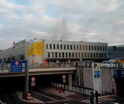 In this image provided by Daniela Schwarzer, smoke is seen at Brussels airport in Brussels, Belgium, after explosions were heard Tuesday, March 22, 2016