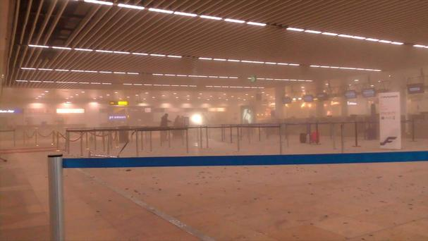 In this photo provided by Ralph Usbeck travellers stand in a smoke filled terminal at Brussels Airport, in Brussels after explosions Tuesday, March 22, 2016.