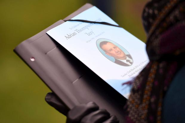A mourner holds a printed tribute at the funeral service for prison officer Adrian Ismay, at Woodvale Methodist Church in Belfast, Northern Ireland March 22, 2016