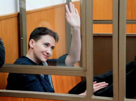 Ukrainian pilot Nadezhda Savchenko waves to journalists from a glass cage inside court, in the town of Donetsk, Rostov-on-Don region, Russia. (AP Photo/Ivan Sekretarev)