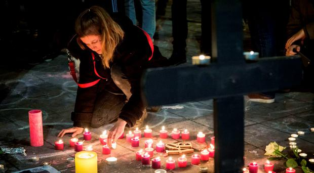 A woman lights a candle among floral tributes, a cross and notes in front of the Bourse of Brussels on March 22, 2016 in tribute to the victims of Brussels Photo:AFP/Getty Images