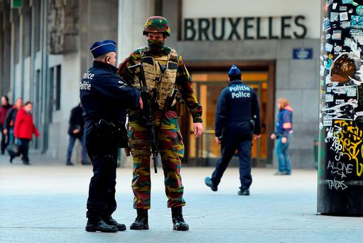 A Belgian soldier speaks to a police officer outside Brussels Central Station as people are allowed in small groups of ten to reach the station in order to take their commuter train following attacks in Brussels. Getty Images