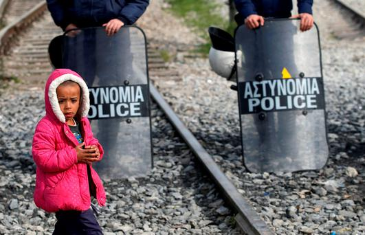 A migrant child walks in front of a police cordon during a protest demanding the opening of the border between Greece and Macedonia in the northern Greek border station of Idomeni. Photo: AP