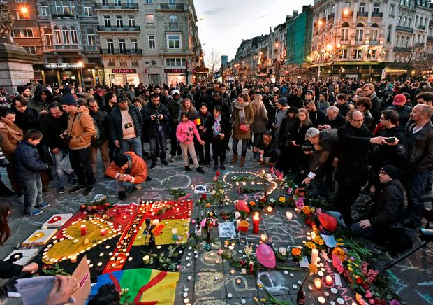 People bring flowers and candles to mourn at Place de la Bourse in the centre of Brussels. Photo: AP