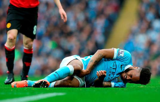 Manchester City's Raheem Sterling lies injured