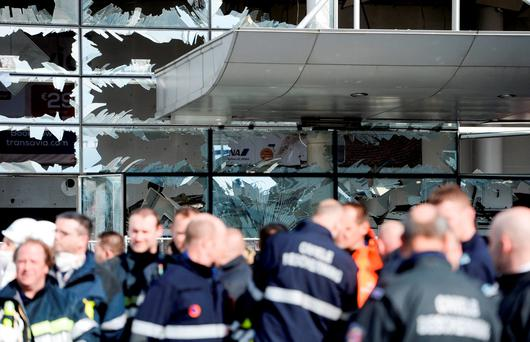 Firefighters and first responders stand in front of the damaged Zaventem Airport terminal in Brussels on Wednesday. (AP Photo/Frederic Sierakowski, Pool)