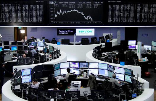 Traders work at their desks in front of the German share price index, DAX board. Photo: Reuters