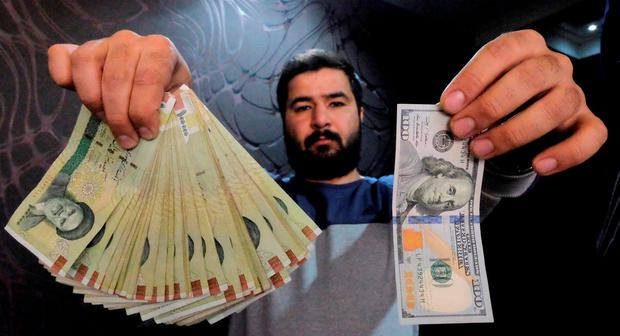 A money changer poses for the camera with a US dollar (R) and the amount being given when converting it into Iranian rials (L), at a currency exchange shop in Tehran's business district