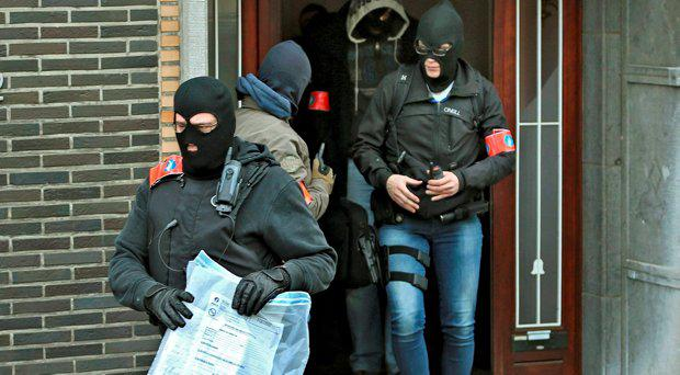 Masked Belgian police remove a package from a building in Anderlecht following Tuesday's bomb attacks in Brussels, Belgium, March 23, 2016