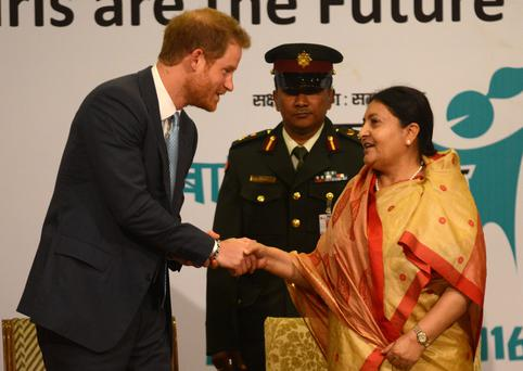 Nepalese President Bidhya Devi Bhandari (R) and Britain's Prince Harry (L) shake hands during the start of the Nepal Girls Summit 2016 in Kathmandu on March 23, 2016. Photo: PRAKASH MATHEMA/AFP/Getty Images)