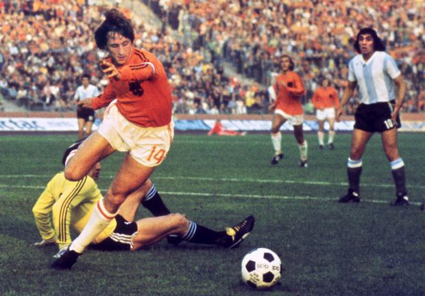 Dutch midfielder Johann Cruyff dribbles past Argentinian goalkeeper Daniel Carnevali on his way to scoring a goal during the World Cup quarter-final in 1974
