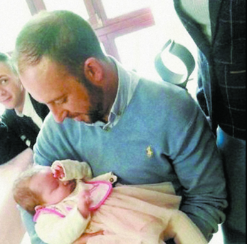 Hero Davitt Walsh holding baby Rioghnach. (Photo courtesy of Derry News )