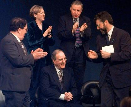 George Mitchell (centre), former US Senator and chairman of the Northern Ireland peace talks, is applauded by fellow recipients of the John F Kennedy Profile in Courage Award – John Hume (left) and Gerry Adams (right) – along with Liz O'Donnell, then Minister of State at the Department of Foreign Affairs, and Paul Murphy, Minister of State of the Northern Ireland Office. The ceremony took place in Boston in December 1998. Photo: AP Photo/Elise Amendola