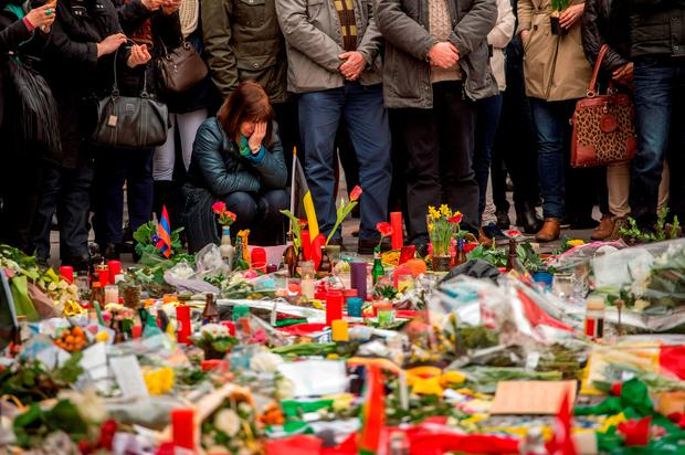 A woman weeps as a crowd gathers in front of a makeshift memorial to pay tribute to the victims of the Brussels attacks on the Place de la Bourse in central Brussels. Photo: AFP/Getty Images