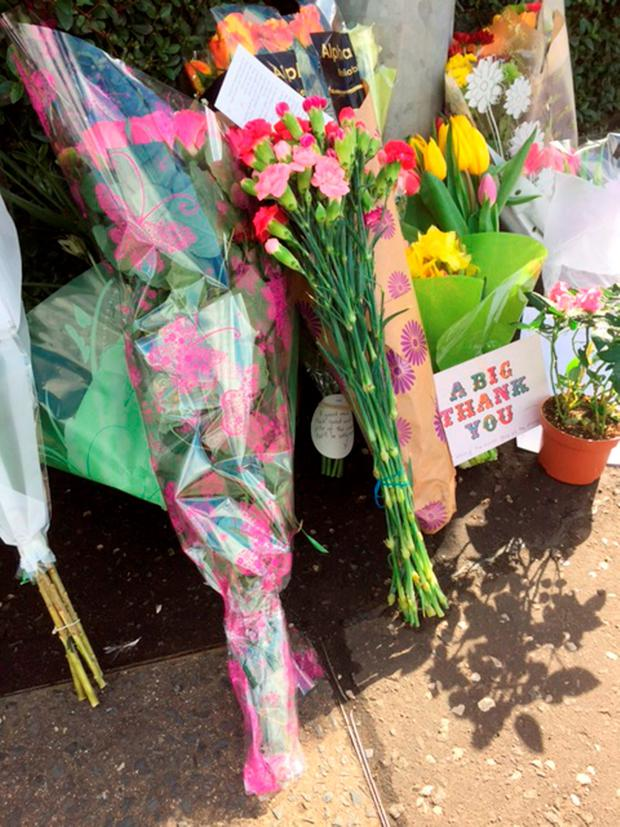 Flowers and messages left after Asad Shah, a shopkeeper, was found seriously injured outside his premises in Minard Road, Glasgow, on Thursday night and later died in hospital Credit: Lucy Christie/PA Wire