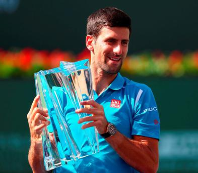 Novak Djokovic holds up the winners trophy after his win over Milos Raonic during day fourteen of the BNP Paribas Open at Indian Wells Tennis Garden. Photo: Julian Finney/Getty Images
