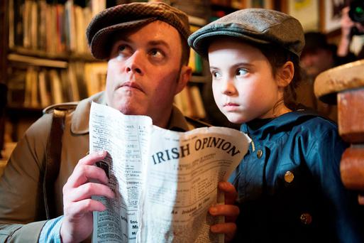 The Rising hit the streets of Galway this week, as one troupe of actors has been staging a series of rather clandestine performances to mark the centenary. Pictured is actor Sean Misteal whispering to Cliodhna O Donoghue, 8, from Ballycullen in Dublin in Ti Neachtain's Galway. Photo: Andrew Downes