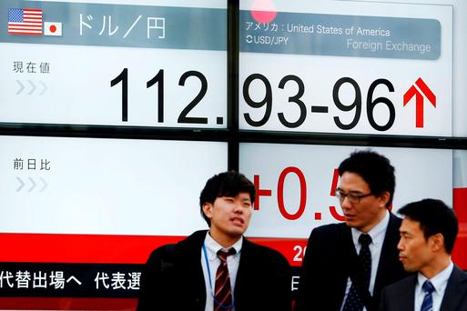 Men stand in front of a screen displaying the Dollar to Yen exchange rate in Tokyo. Photo: Reuters