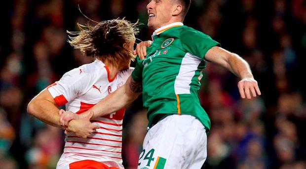 Republic of Ireland's Ciaran Clark and Switzerland's Michael Lang battle for the ball in the air. Photo: Brian Lawless/PA Wire