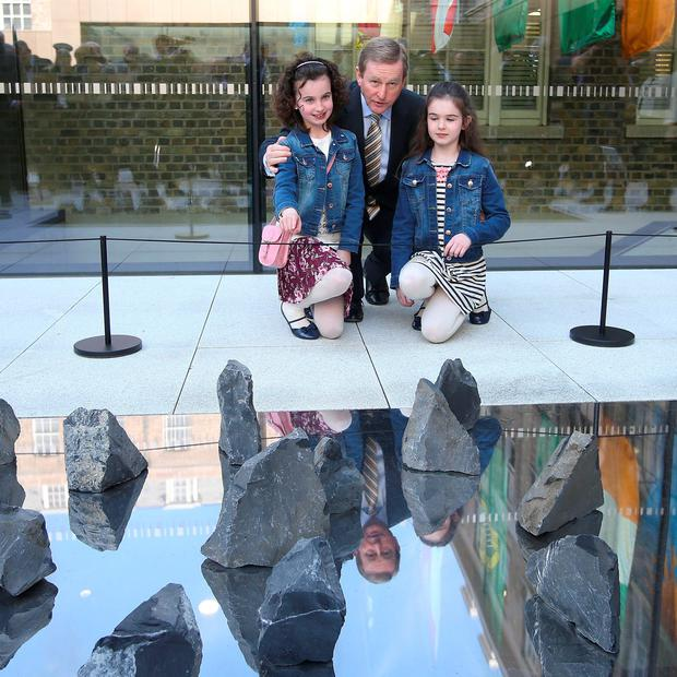 Taoiseach, Enda Kenny, TD, with Megan, left, 8 and her sister, Laura Jones, 10, in front of a memorial titled,