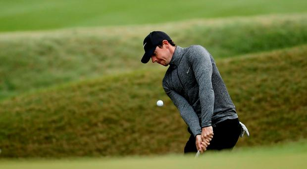 Rory McIlroy, of Northern Ireland, chips onto the sixth green during the round of 16 play against Dustin Johnson at the Dell Match Play Championship golf tournament at Austin County Club