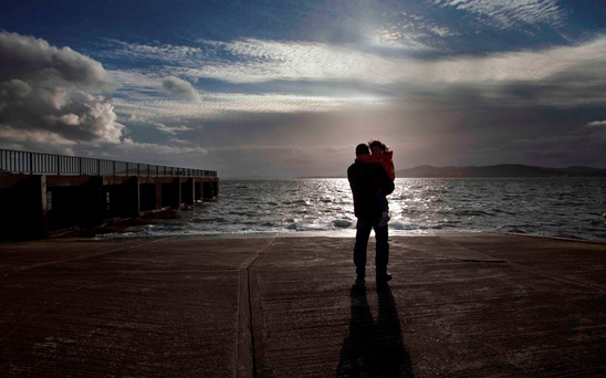A father and daughter look out across Lough Swilly in Co Donegal from the spot on the pier where the five family members drowned Photo: RollingNews.ie