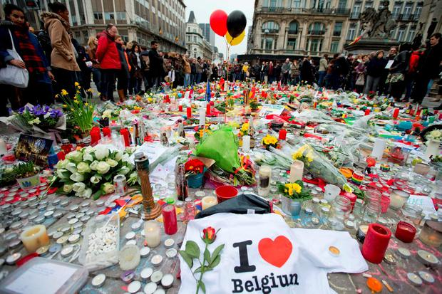 Three balloons in the colors of the Belgian flag fly as people mourn for the victims of the bombings at the Place de la Bourse in the center of Brussels Photo: AP