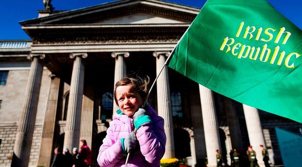 Grace Nic Mhathuna, six, from Dublin, waves a flag outside the GPO: Maxwells/PA Wire
