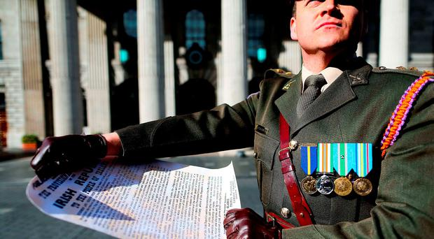 Captain Peter Kelleher from the 27th Infantry Battalion, reading the Proclamation at the GPO: Maxwells/PA Wire