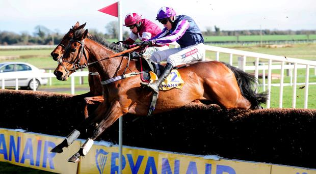 Kylemore Lough ridden by Barry Geraghty (near side) jump the last to win the Ryanair Gold Cup Novice Steeplechase during day one of the Easter Festival at Fairyhouse Racecourse, Co. Meath