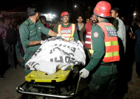 Rescue workers move a body from the site of a blast outside a public park in Lahore, Pakistan REUTERS/Mohsin Raza