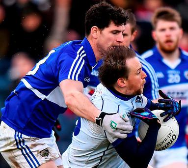 Seanie Johnston is tackled by Laois's Brendan Quigley. Photo: Ramsey Cardy / Sportsfile