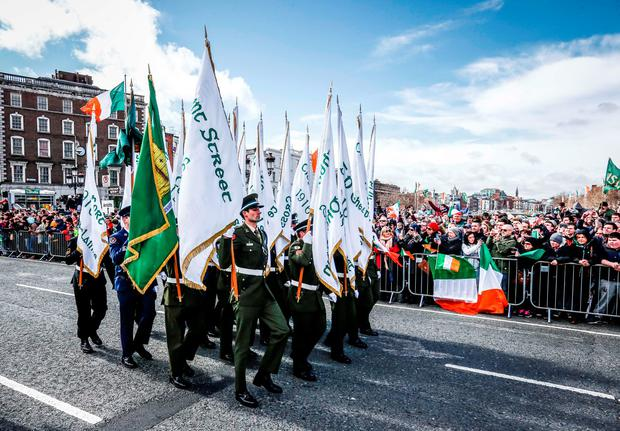 Members of the Defence Forces carry the flags of the garrisons which participated in the 1916 Rising across O'Connell Bridge. Photo: Conor McCabe