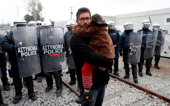 A migrant holds a child as he stands in front of Greek police during a protest at a makeshift camp at the Greek-Macedonian border near the village of Idomeni, Greece. Photo: Marko Djurica/Reuters