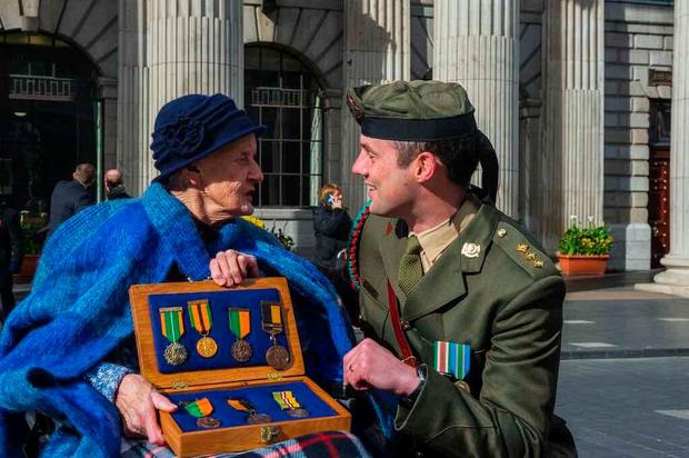 The Defence Forces' Press Officer seen with Sheila O'Leary, 94, whose father Thomas Byrne fought in GPO with Irish Volunteers.