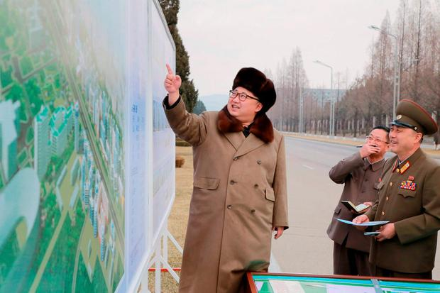 North Korean leader Kim Jong Un (L) speaks at an event declaring the construction of Ryomyong Street, in this photo released by North Korea's Korean Central News Agency (KCNA)