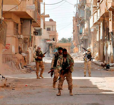 Syrian government troops patrol Palmyra following its recapture from Isil on Sunday Photo: REUTERS/SANA/Handout via Reuters