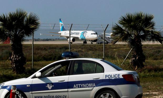 Police stand guard at Larnaca Airport near a hijacked Egyptair Airbus A320 , March 29, 2016. REUTERS/Yiannis Kourtoglou