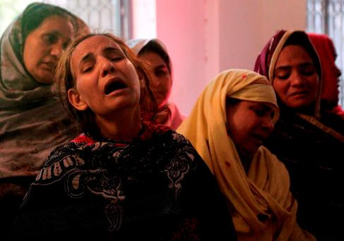 Family members mourn the death of a relative, who was killed in a blast that happened outside a public park on Sunday, in Lahore, Pakistan. Reuters/Mohsin Raza