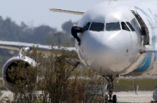 A man climbs out of the cockpit window of the hijacked Egyptair Airbus A320 at Larnaca Airport in Larnaca, Cyprus. Reuters/ Yiannis Kourtoglou