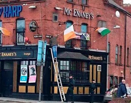 Social media image showing a PSNI officer holding a ladder for a man raising a flag on the Falls road in Belfast