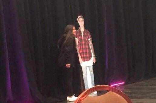 A fan meets a cardboard cutout of Justin Bieber