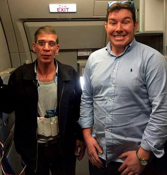 Seif al-Din Mustafa, displaying his fake explosive belt, poses for a photo with British passenger Ben Innes from Leeds.